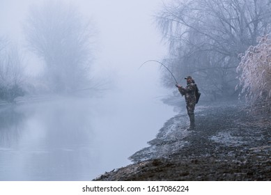 Fisher man fishing with spinning rod on a river bank at misty foggy winter, spin fishing, prey fishing