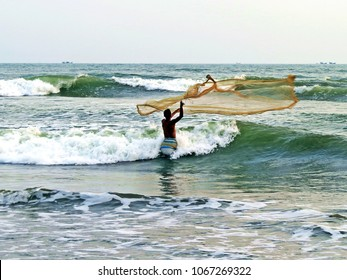 fisher man throwing his net for the first catch of the day, Cox Bazar, Bangladesh