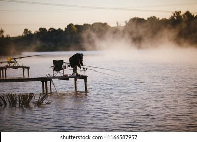 Fisher on the wooden pier to fish in the morning on sunrise. Feeder carp fishing.