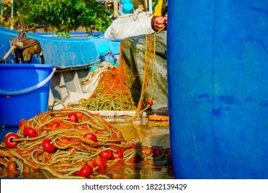 Fischer in Gummi Hose und Kofferraum sitzt in seinem Boot und sammeln Angelnetz für Angeln auf offener See.