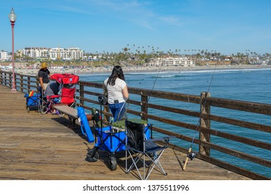 Fisher trying to catch fish on the Oceanside Pier during blue summer day, Oceanside, northern San Diego County, California. Wooden pier on the western United States coastline. 03/22/2019