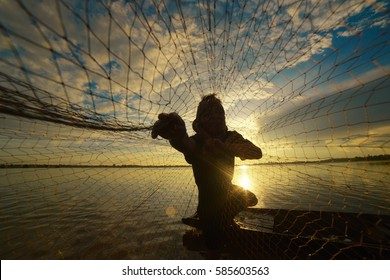Fisherman in action, Thailand. Silhouette of fishermen using nets to catch fish at the lake in the morning.