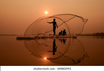 Fisherman in action when fishing in the lake , Thailand