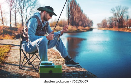 Fisherman angling on the river. Angler sitting on the riverside and trying to catch a fish. Sport, recreation, lifestyle