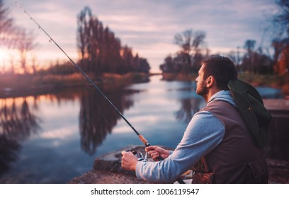 Fisherman angling on the river. Fisherman standing on the riverside and trying to catch a fish. Sport, recreation, lifestyle