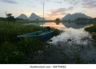 Fisherman boat by the lakeside during sunrise.