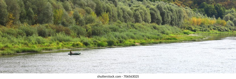 fisherman in boat in good weather in autumn catches fish on river