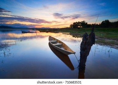 A fisherman boat in a lake during sunset, with reflection on the smooth surface water
