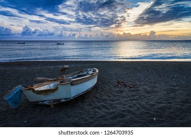 Fisherman boat on a beach during a beautiful sunset