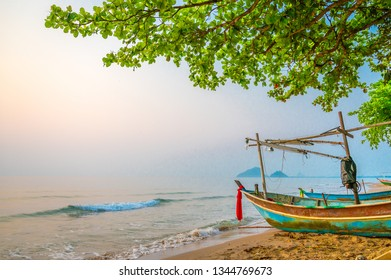 Fisherman boat on the beach and green leaves