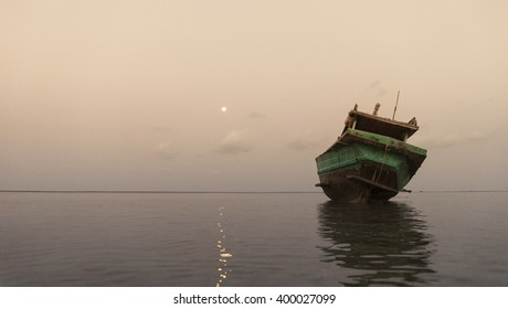 Fisherman boat resting on the shore at dawn
