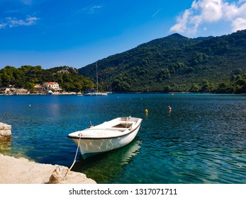 Fisherman boat in the small bay of island Mljet, hot sunny summer morning in the typical old village, turquoise water and green mountains on the background, mediterranean coast, Croatia