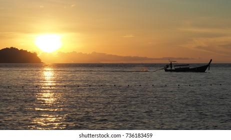 Fisherman boat and sunrise