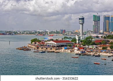 Fisherman boats in front of Kivukoni fish market with Port control tower and Skyscrapers Behind, Dar Es Salaam, Tanzania