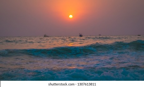 Fisherman boats in north Goa, India near Calangute beach at sunset. Touristic attraction for beach summer vacations in India by the Arabian Sea. Beautiful sunset with full sun in Goa.