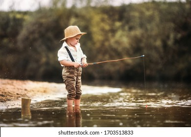 A fisherman boy stands in the river with a fishing rod and catches fish