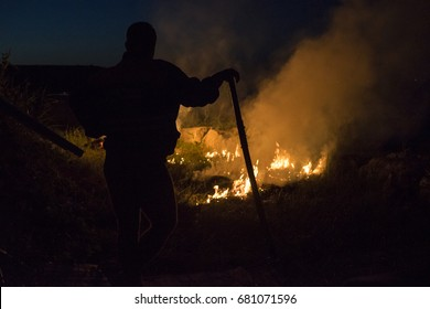 Fisherman burning weeds/man silhouette standing in front of a fire and leaning on a bracket during the night.