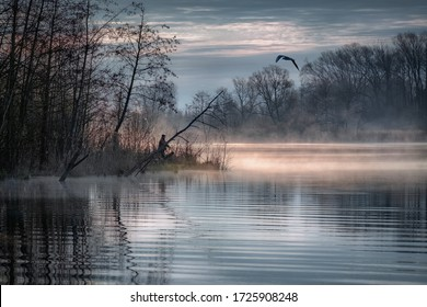 Fisherman in the bushes on an early foggy morning on the lake.