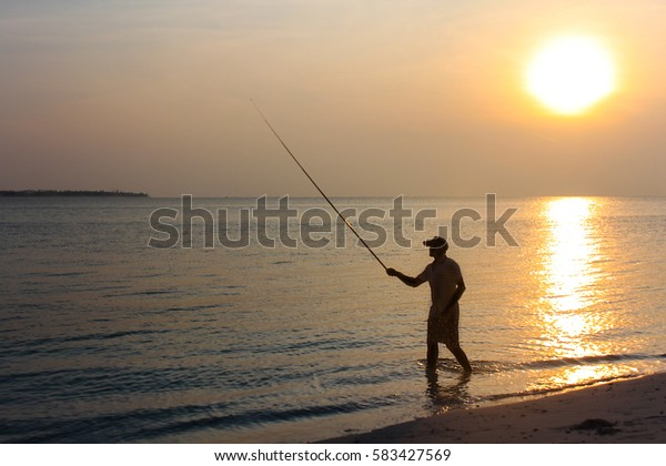 Fisherman by the shore catching fish with a rod at sunrise