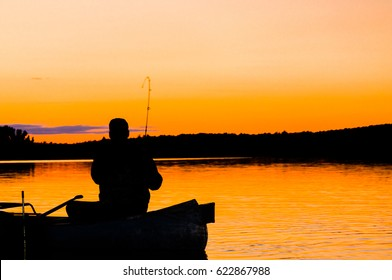 A fisherman in a canoe is silhouetted against the blazing orange sky of a setting sun in the Boundary Waters Canoe area of Northern Minnesota