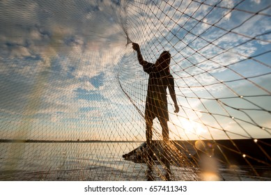 a fisherman cast a net at lake in the moring time , silhouette light
