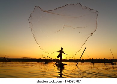 Fisherman casting his net at sunrise on the Mekong River in Thailand.