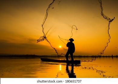 Fisherman casting his net at sunrise