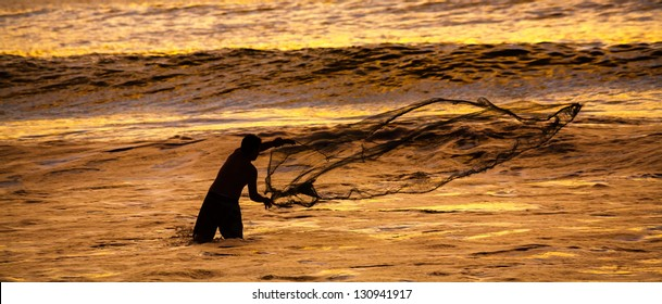 Fisherman casting his net at the sunset in Cerro Azul, Lima, Peru