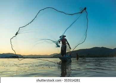 Fisherman casting his net at the sunset at Mae Klong River, Thailand