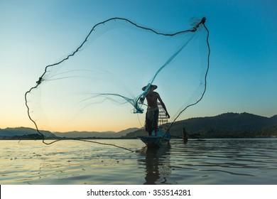 Fisherman casting his net at the sunset at Mae Klong River, Thailand