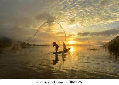 A fisherman casting a net into the water during on the mist at sunrise