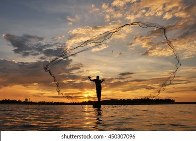 A fisherman casting a net into the water during on  sunset