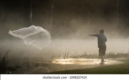 Fisherman casting net on foggy river