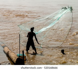 A fisherman casts his net