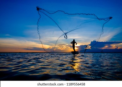 Fisherman catch fish by his fishing net during sunset and twilight sky
