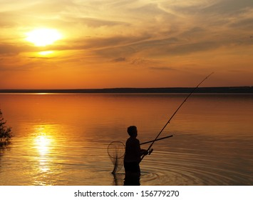Fisherman catches fish by spinning on the lake at sunset