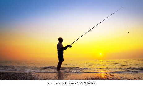 Fisherman catches a fish. Hands of a fisherman with a spinning rod reel in hand closeup