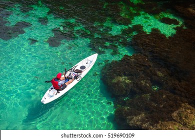 Fisherman catches a fish on a fishing kayak view from above.