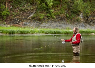 A fisherman catches fish on the river using fly fishing gear. Angler stands in  water above his knees, wearing a waterproof jumpsuit.