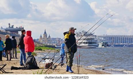 Fisherman catches a fishing rod on the concrete embankment of the Volga River against the background of the city. Nizhny Novgorod, Nizhnevolzhskaya embankment, Russia July 26, 2017