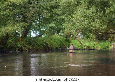 Fisherman catches a fly on the beautiful forest river.