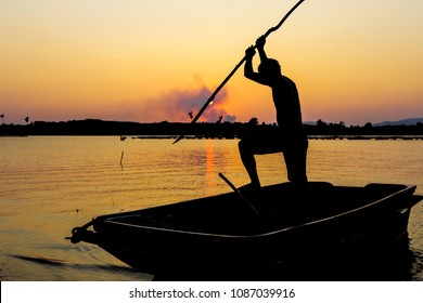 Fisherman catching the fish by spear in silhouette picture style