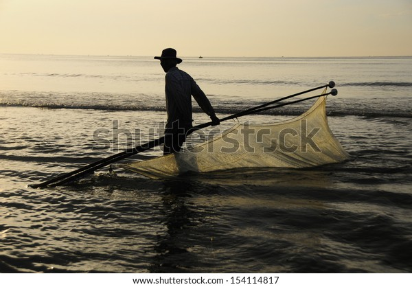 """Fisherman catching plankton """"Ruoc"""" with fishnet at dusk on the beach in southern Viet Nam"""