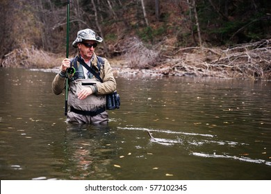 Fisherman caught grayling and pulls him out of the river