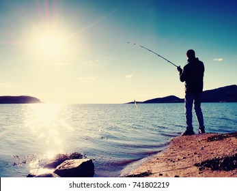 Fisherman check fishing line and pushing bait on the rod, prepare himself and throw lure far into peaceful water. Fisherman silhouette at sunset