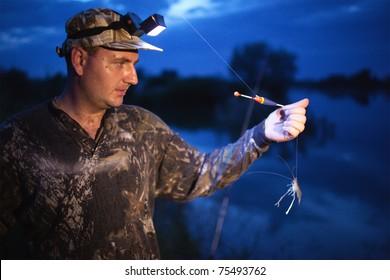 Fisherman at dusk preparing bait