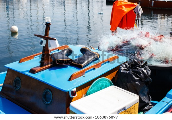 fisherman equipment on boat: rubber boots, network
