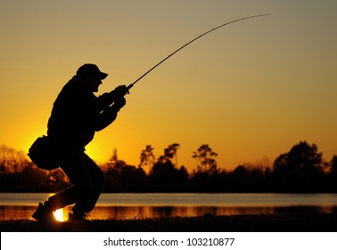 A fisherman fight against a bass at sunset