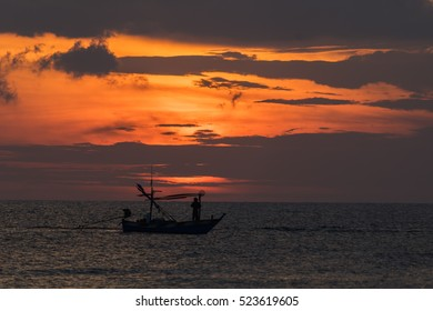 A fisherman and fishing boat at dawn on the ocean in Thailand.