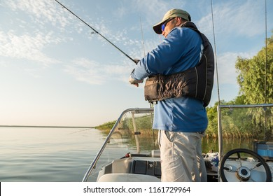 A fisherman in a fishing boat on a river is fishing